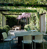 An aluminium modern take on the traditional cane-backed chair surrounds this square table under an ivy-covered pergola