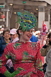 Woman in a vintage dress, green gloves, and a hat made out of peacock feathers in the Easter Parade on Fifth Avenue in New York City