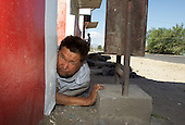 A drunken man collapses on the steps of a kiosk in Kyzyl, capital of the Tuva Republic, southern Siberia, Russia. Alcoholism is rife in the region.