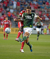 Portland defender David Horst (12) clears the ball away while being pressured by Chicago forward Dominic Oduro (8).  The Portland Timbers defeated the Chicago Fire 1-0 at Toyota Park in Bridgeview, IL on July 16, 2011.