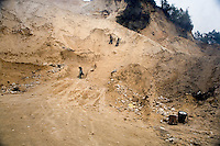 Workers gather sand to be used in road construction in rural Yuanyang County, Yunnan Province, China. The Yunnan government has been building modern freeways and highways throughout the province to improve trade and and tourism in the region.