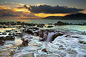 The ocean flowing back into a blowhole opening at sunset after the spouting eruption occurred, Kauai, Hawaii, USA.