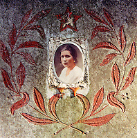 Portrait of a young woman on a decorated grave stone in a cemetery of the Soviet army.  The Cold War, which formed part of the collective consciousness of post war Europe from 1945 until 1989 dominated the military and political landscape.  Often highly charged with nationalistic zeal, Soviet rhetoric and paranoia, relics of the Cold War remain as testaments to the covert era within Eastern Europe.. CHECK with MRM/FNA