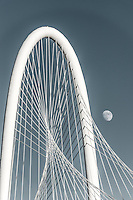 Dallas arch of Margaret Hunt Hill Bridge with the moon in a cyan