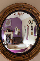 The white and purple bathroom is reflected in the convex mirror which hangs on one wall