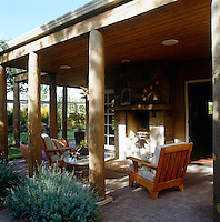 Comfortable wooden garden chairs and a table surround an exterior fireplace on the covered terrace of a contemporary house in New Mexico