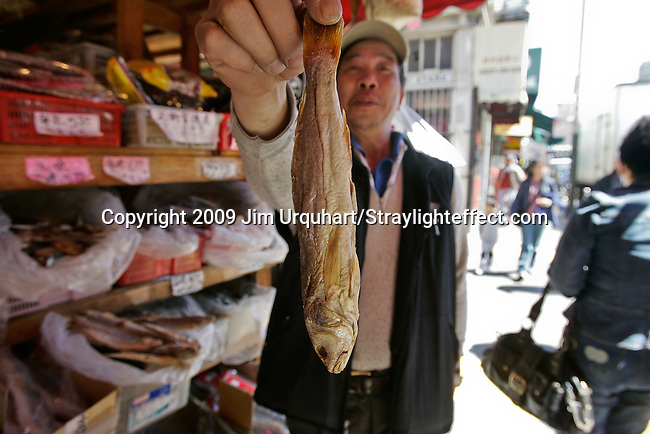 A shop keeper shows off his dried fish he sells in the fish market of the Chinatown district of San Francisco, California.  Jim Urquhart/Straylighteffect.com