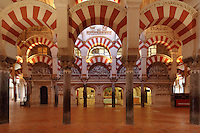 The hypostyle prayer hall, area built in the 10th century under Al-Mansur, 987-988, with 5 reliefs by Fray Juan Alvarez de Toledo, 1523-37 representing scenes of Christ's Passion, behind the altar of the cathedral, in the Cathedral-Great Mosque of Cordoba, in Cordoba, Andalusia, Southern Spain. The hall is filled with rows of columns topped with double arches, a horseshoe arch below a Roman arch, in stripes of red brick and white stone. The first church built here by the Visigoths in the 7th century was split in half by the Moors, becoming half church, half mosque. In 784, the Great Mosque of Cordoba was begun in its place and developed over 200 years, but in 1236 it was converted into a catholic church, with a Renaissance cathedral nave built in the 16th century. The historic centre of Cordoba is listed as a UNESCO World Heritage Site. Picture by Manuel Cohen
