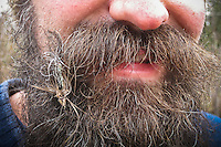 A fly fisherman displays a fly in his beard the fly was made using his own beard hair and a ruffed grouse feather found while steelhead fishing in Michigan.