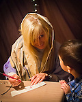 Garden City, New York, USA. December 6, 2013. At the Town Scribe stall at A Night in Bethlehem, visitors experience what it might have been like the night Jesus was born. Families visit different shops and participate in projects. Finally the children and adults experience the nativity scene at the manger, with Mary, Joseph, and baby Jesus, on the first Christmas. This free annual Advent event is December 6, 7, and 8, at the Lutheran Church of the Resurrection, on Long Island.