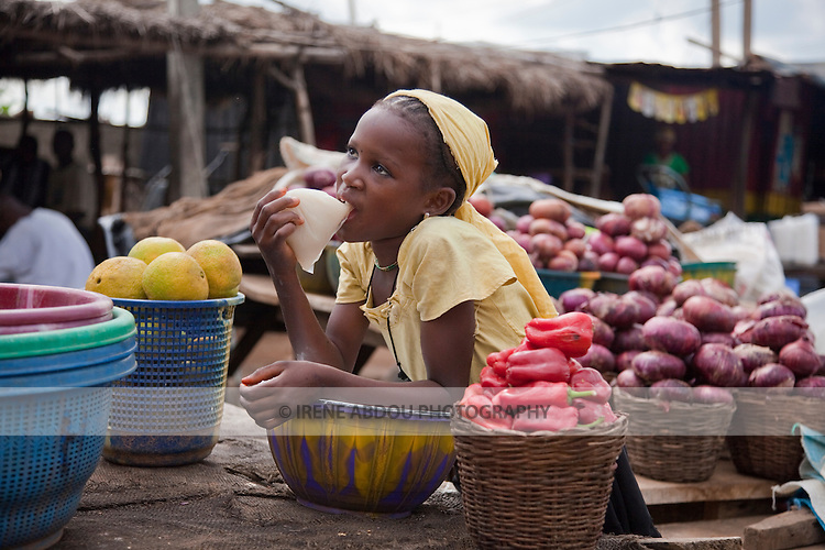"A young Fulani girl drinks ""kunu"" from a plastic bag, while manning fruit and vegetable table at a roadside market in Nigeria's Niger State.  Kunu is a delicious millet drink spiced with ginger."