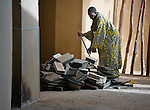 A man cleans up boxes that once held ancient documents at the Ahmed Baba Institute in Timbuktu, Mali. The documents were burned by Islamist radicals who seized control of the city in 2012. Most of the ancient documents in the city went undetected or were smuggled out of Timbuktu in an elaborate rescue operation. The city was liberated by French and Malian soldiers in early 2013.