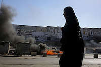 Palestinian woman passes in the clashes zone while palestinian clalsh with Israel Defense Forces after the funeral held for three Palestinians killed during IDF operation at Kalandia refugee camp on August 26, 2013 in Ramallah, West Bank. Photo by Oren Nahshon