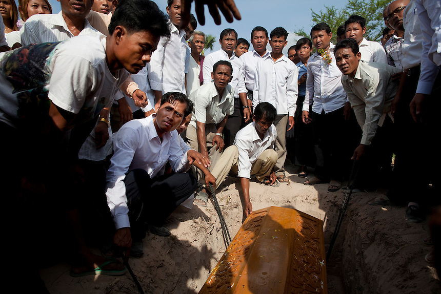 The coffin of slain environmental activist Chut Wutty is lowered into ...
