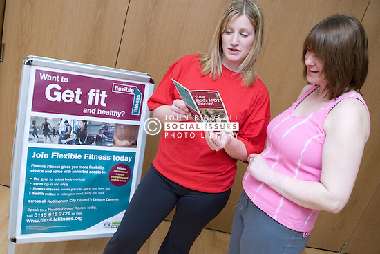 Fitness instructor going through a body MOT leaflet with a member at her sports leisure centre,
