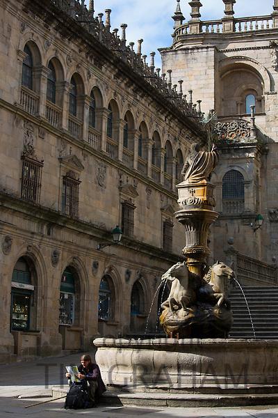 Pilgrim on St James pilgrimage by Dos Cavalos horse fountain Praza das Praterias, Santiago de Compostela, Galicia, Spain