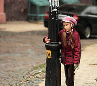 Young girl, holding toy dragon,  taking a rest walking up a steep hill in Kiev, Ukraine, 2008