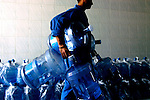 A worker at the Al-Safa Company carries empty bottles into the factory to be refilled in Baghdad. Many upper-class families have purified water dispensers in their homes.