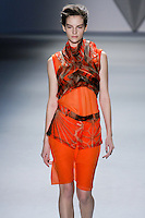 Sara Blomqvist walks runway in a tangerine silk chiffon vault print flange harness over silk chiffon sleeveless dress with stand melton collar, trim detail and vault print zip-front peplum tangerine techno stretch bermuda short, from the Vera Wang Fall 2012 Vis-a-gris collection, during Mercedes-Benz Fashion Week Fall 2012 in New York.
