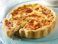 Quiche Loraine on a blue board with a slice being lifted