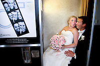 Bride and groom stick their tongues out at each other while having their photos made in a genuine photo booth. (Photo by Scott Eklund/Red Box Pictures)
