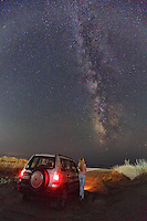 A woman beside a Mitsubishi Pajero looking at the Milky Way