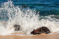 White water splashes on boulders from a wave breaking on the shoreline of Ke Iki Beach, North Shore, O'ahu.