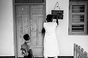 Mathumita's son looks on while she leaves a note on the health centre's board before going out on field visits in Punaineeravi village in Kilinochchi in Northern Sri Lanka. Photo: Sanjit Das/Panos