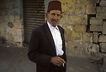 An old man wears a fez and smokes a cigarette on a street in southern Lebanon in 1981.