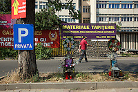 Romania. Iași County. Iasi. A man walks on the road. Blue sign for a private parking. Two colorful funeral wreaths and pictures for two young men deceased on car accidents. An advertising banner for a private company which uses as a satire symbols from the old communist time - a crown, a hammer and a tool - in her marketing stategy. Iași (also referred to as Iasi, Jassy or Iassy) is the largest city in eastern Romania and the seat of Iași County. Located in the Moldavia region, Iași has traditionally been one of the leading centres of Romanian social life. The city was the capital of the Principality of Moldavia from 1564 to 1859, then of the United Principalities from 1859 to 1862, and the capital of Romania from 1916 to 1918. 11.06.15 © 2015 Didier Ruef