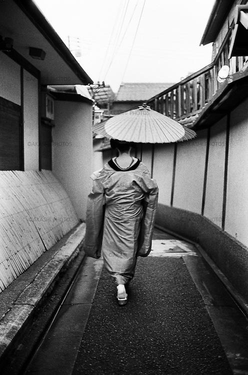 Geisha walks with her umbrella in Kyoto.