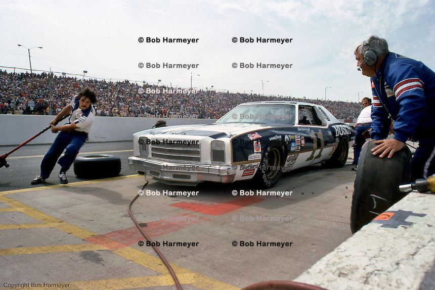 Jeff Hammond (left) swings the jack around the front of Cale Yarborough's Chevrolet while Junior Johnson (right) waits to roll a tire to the car during a pit stop in a 1980 NASCAR race at Atlanta Motor Speedway near Atlanta, Georgia.