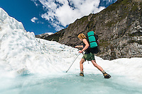 Climber walking through melt water pool on Franz Josef Glacier, Westland National Park, West Coast, New Zealand