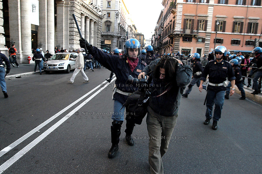 Roma  25 Ottobre 2005.Manifestazione degli studenti universitari contro il DDL Moratti..La Polizia carica  e picchia gli studenti,  davanti Palazzo Chigi, sede del Governo Berlusconi.Un agente di polizia aggredisce un fotoreporter.Rome 25 October 2005.Demonstration of university students against the DDL Moratti..The police charged and beat the students in front of Palazzo Chigi, seat of the Berlusconi government.A police officer attacks a photographer