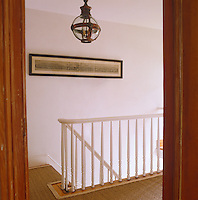 A copper and glass lantern and an old print decorate the otherwise plain landing