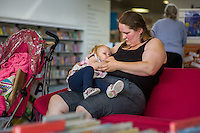 A mother breastfeeding her toddler in a library.Image from the breastfeeding collection of the &quot;We Do It In Public&quot; documentary photography picture library project: <br />  www.breastfeedinginpublic.co.uk<br /> <br /> <br /> Hampshire, England, UK<br /> 19/06/2015<br /> <br /> &copy; Paul Carter / wdiip.co.uk