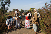 Junior community reporter Sunita (center), 22, interviews Bhagwat Dewedi (left), 48, a panchayat leader (village elder), as he walks home from his 25 acres of farming land in Chitrakoot, Uttar Pradesh, India on 5th December 2012. Sunita and her husband, now sick with TB and unable to work, were estranged from their families because they married against the family's wishes, so Sunita, who had finished her high-school education, supports her husband on the income she makes as a journalist. She makes about 4500 rupees a month. Photo by Suzanne Lee for Marie Claire France.