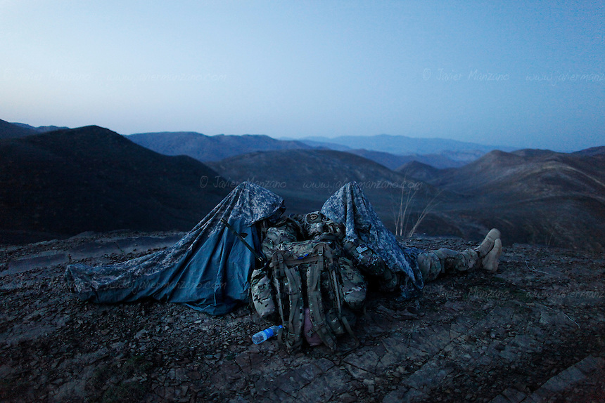 Members of 3rd Platoon, Comanche Company 1st of the 501st Parachute Infantry Regiment rest after reaching the summit of a mountain after a 4-day mission with members of the Afghan National Army in the ridges that overlook the border with Pakistan. The purpose of the mission was to survey the area for possible insurgency activity as well as to search surrounding villages for possible weapons caches. The area is a well-known trafficking route for weapons and insurgents coming into Afghanistan from the lawless North Waziristan mountains of Pakistan. © Javier Manzano