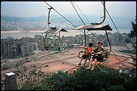 """Fengdu, China, August 2003.Chinese tourists visiting the old city of Fengdu, already half-destroyed to allow the Three Gorges Dam project to be completed. In the background, the """"new"""" city on the right bank of the Yangtze Kiang river.."""