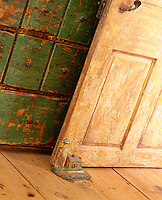 A distressed wooden door is held open against a  green-painted set of drawers in similar condition by a cast iron model of a lighthouse
