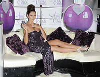 Amy Childs.The photocall to launch her debut fragrance in collaboration with Jigsaw, Aura bar & nightclub, London, England..August 15th, 2012.full length purple strapless dress slit split sequins sequined hair up bun sofa couch sitting silver sandals shoes hand arm.CAP/CAN.©Can Nguyen/Capital Pictures.