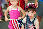 Waving American Flag, young boy and girls watching Merrick Memorial Day Parade on May 28, 2012, on Long Island, New York, USA. America's war heroes are honored on this National Holiday.