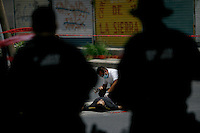 06/02/2010..CSI personnel examine the body of a man who was shot in front of a High-School in downtown Ciudad Juarez.