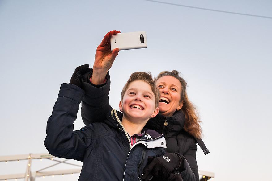 Nederland, Amsterdam, 4 jan 2015<br /> Kunstijsbaan op het Museumplein. Een leuke attractie, zeker als het mooi weer is.  Familieuitje voor het hele gezin.<br /> Moeder en zoon maken een selfie op de ijsbaan.<br /> <br /> Foto: (c) Michiel Wijnbergh