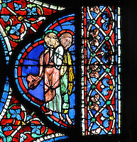 Two apostles, with expressions of sadness, to the right of the scene of the apostles carrying the coffin of Mary, from the Funeral of Mary in the Glorification of the Virgin stained glass window, in the nave of Chartres Cathedral, Eure-et-Loir, France. This window depicts the end of the Virgin's life on earth, her dormition and assumption, as told in the apocryphal text the Golden Legend of 1260. Chartres cathedral was built 1194-1250 and is a fine example of Gothic architecture. Most of its windows date from 1205-40 although a few earlier 12th century examples are also intact. It was declared a UNESCO World Heritage Site in 1979. Picture by Manuel Cohen