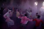Devotees dance in the cloud of  gulal (powdered colour) inside the temple of Radha (Radhika) in Barsana, Uttar Pradesh, India on the day of Lathmar holi. Lathmar holy is celibrated 7 days before the actual holi day.