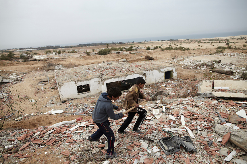 Two boys play argue over a shovel in the former Israeli settlement of Elei Sinai in northern Gaza. Men and children come here daily to gather building materials even though the area is a no-go zone and dozens have been maimed and killed by Israeli soldiers.