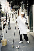 Man sweeping the street in front of his restaurant in New Orleance