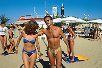 Italy. Province Emilia-Romagna. Rimini. A man and a woman, both italian tourists, dance on the sandy beach. Life in the summer on the sand beach. On the roof of the beach's restaurant, a bottle of Coca Cola as advertising campaign. Rimini is located on the Adriatic Sea and is one of the most famous seaside resorts in Europe, thanks to its 15 km-long sandy beach. 17.07.99 © 1999 Didier Ruef