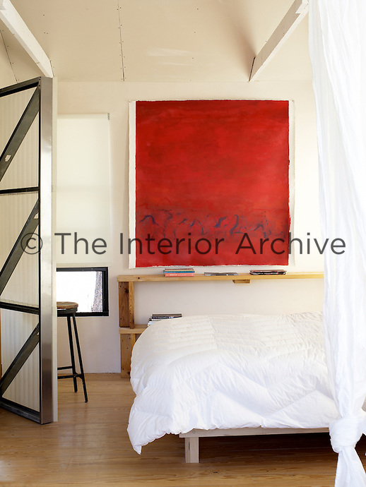 With stunning simplicity a large monchrome painting is pinned above the bed in the white-painted bedroom